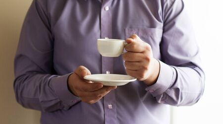 Businessman holding a cup of delicious coffee aroma photo