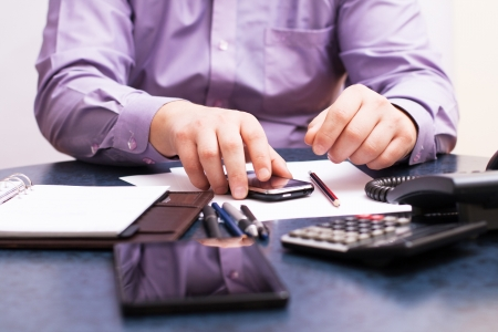 exerted: Businessman sitting at office desk and plans its work Stock Photo