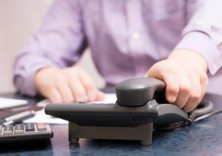 Geschäftsmann wählt die Nummer und reden über das Telefon im Büro Standard-Bild - 18298418