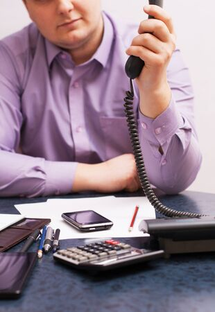 Businessman dials the number and talking on the office phone photo