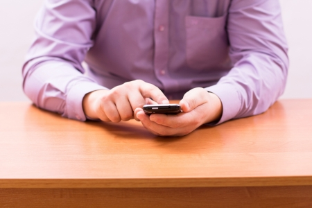 Businessman writes a message and looking for contacts on your mobile phone Stock Photo