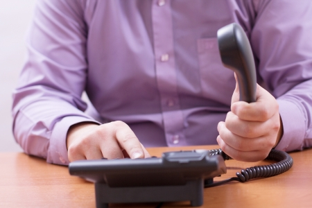 touchtone: Businessman dials the number and talking on the office phone Stock Photo