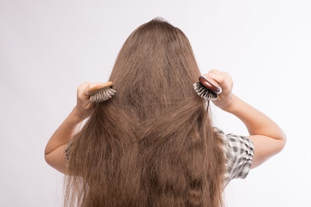 Young beautiful woman combing her luxuriant hair photo