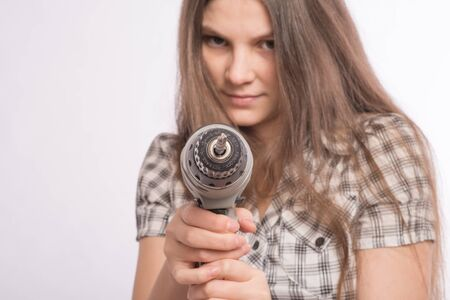 Young energetic woman is using an electric drill Stock Photo - 18547393