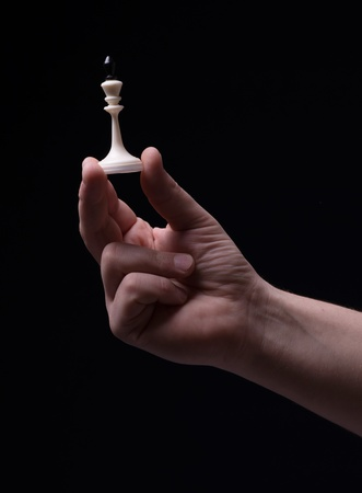 Chess in hand on a black background photo