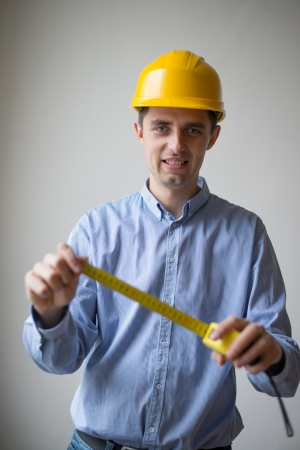 The builder in a helmet with a meter Stock Photo - 18558134