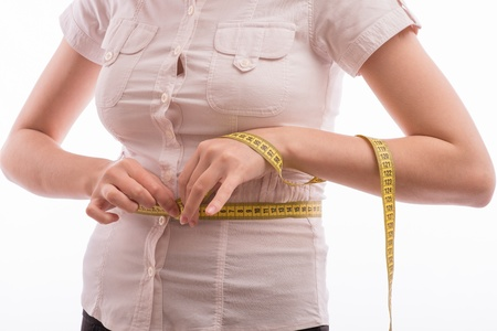 Happy young woman measuring her waist Stock Photo