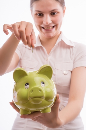 A woman throws a small change in a piggy bank Stock Photo - 18529252