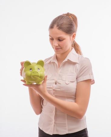 A woman holds a stylish piggy bank Stock Photo - 18529230