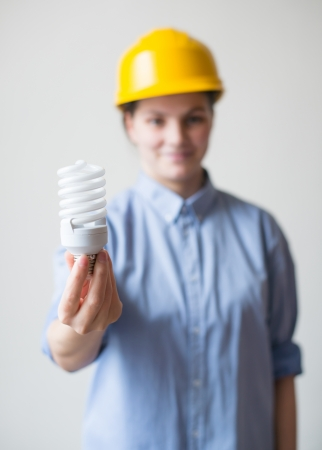 A young woman in a helmet holding a light bulb photo