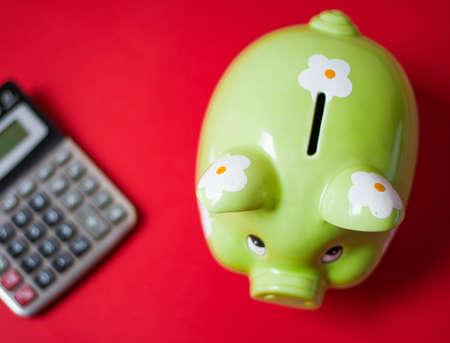 banco mundial: Hucha verde y calculadora sobre un fondo rojo