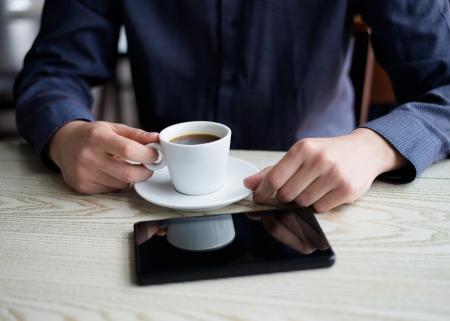 Geschäftsmann mit einem Tablett und Kaffee trinken