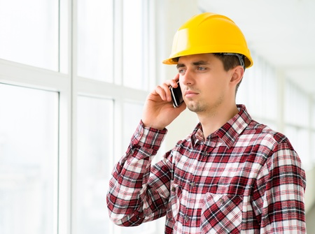 engineer in a helmet uses a smart phone and digital tablet Stock Photo