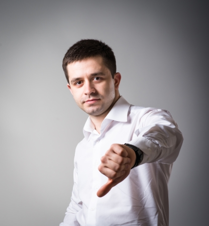 young man showing thumbs down on a gray background photo