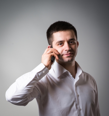 Close up of man using mobile smart phone on a gray background photo