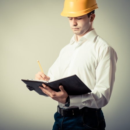 engineer in a helmet writes in a notebook  on a gray background photo