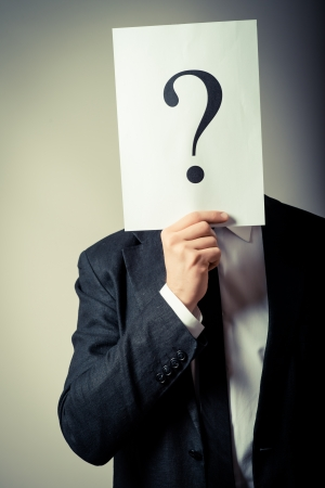 Young businessman holding a white billboard with a question mark on it Standard-Bild