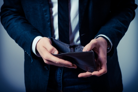 spendings: Businessman well-dressed with empty wallet