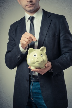 businessman putting a coin into a piggy bank on a gray background photo