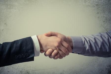 Handshake - Hand holding on gray background photo