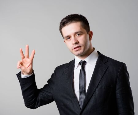three persons only: Happy smiling business man showing three  fingers