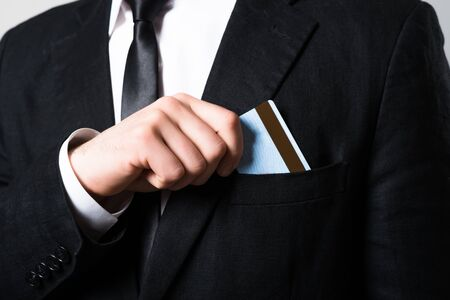 businessman put or take out credit card in pocket, close up on a gray background photo