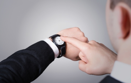 Mans hand in the suit pointing on his watch on a gray background