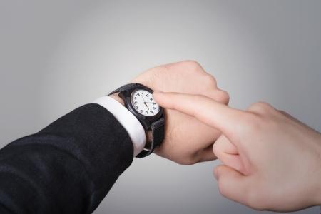 punctual: La mano del hombre en el juego que señala en su reloj sobre un fondo gris Foto de archivo