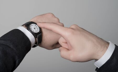 Mans hand in the suit pointing on his watch on a gray background photo