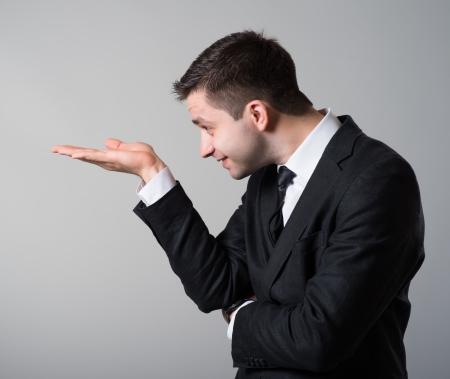 Mann, der etwas auf der Handfläche der anderen Hand auf einem grauen Hintergrund Standard-Bild