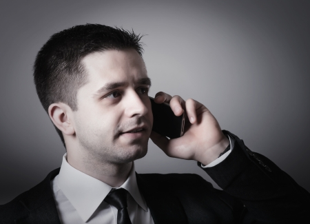 Close up of young businessman using smart phone on gray background photo