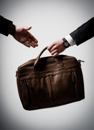 businessman passes briefcase photo