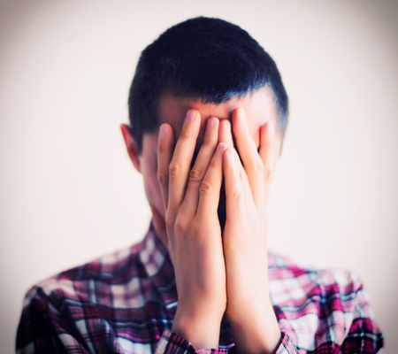 Desperate young man covering with his head in his hands photo