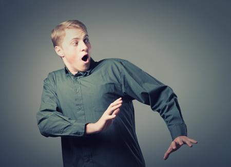 asustado: Hombre joven que retiene sus manos de miedo Foto de archivo
