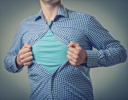 Businessman showing a superhero suit underneath his suit Stock Photo
