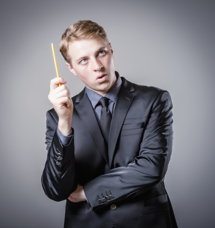 bad planning: young man scratches his head in pencil Stock Photo