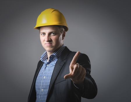 young engineer in a helmet shows the index finger photo