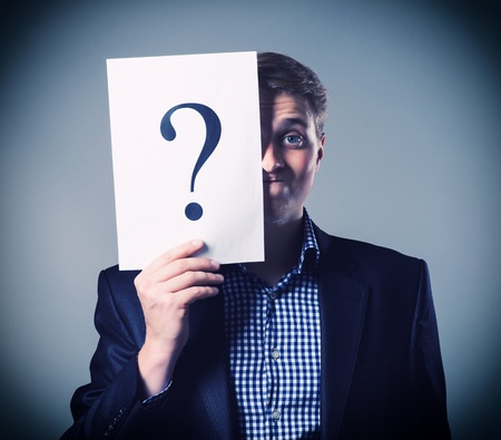Young businessman holding a white billboard with a question mark on it photo