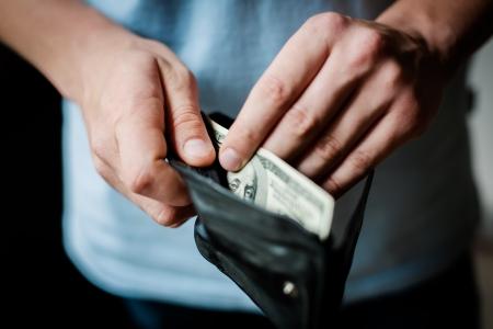 Man bekommt Geld aus der Brieftasche