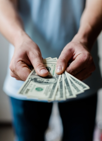 Man holding American dollars in  hands