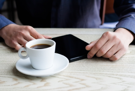 businessman using a tablet and drinking coffee photo