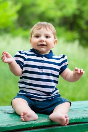 little boy sitting on a bench photo