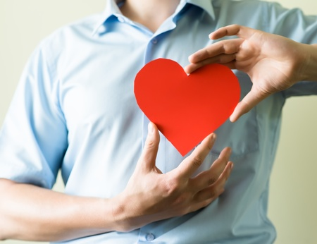 hand red: young man holding a heart in his hands Stock Photo