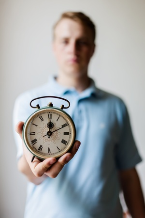 man holding an alarm clock in hands photo