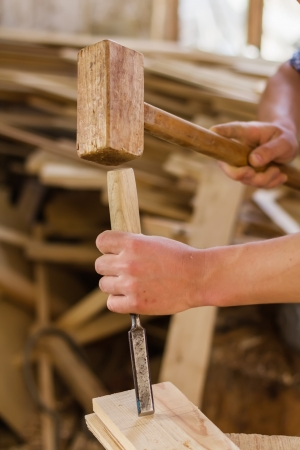hand working in wood chisel carpenter tool hammer