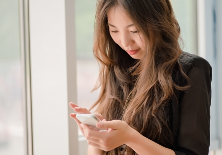 uses: beautiful young woman uses a smartphone