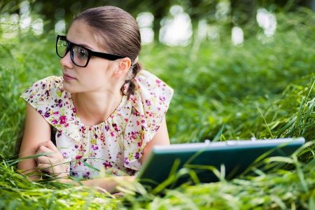 uses: young beautiful woman uses a laptop outdoors Stock Photo