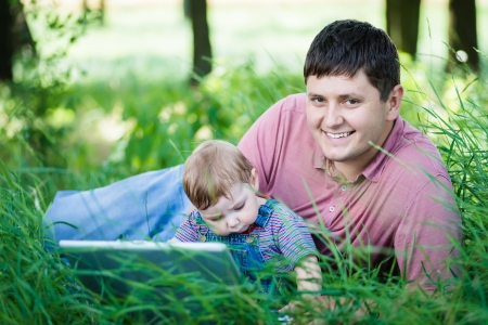 father with his son on nature with laptop photo