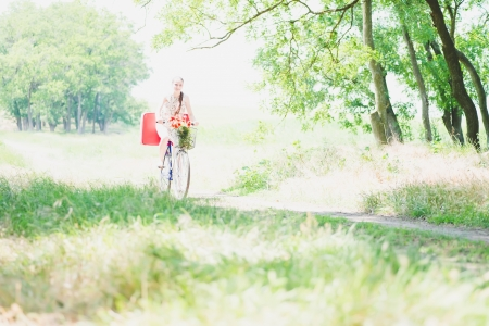 girl with red suitcase rides a bicycle photo