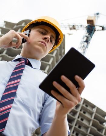 Ingenieur in einem Helm mit einem digitalen Tablette